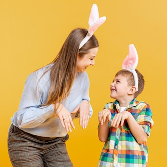Mãe e filho imitando coelho