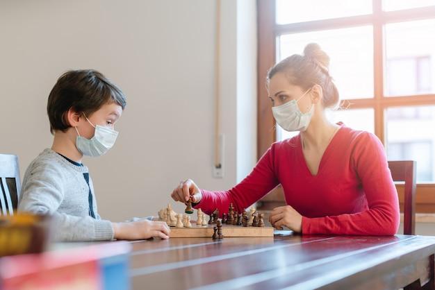 Mãe e filho jogando xadrez para matar algum tempo durante o toque de recolher em crises