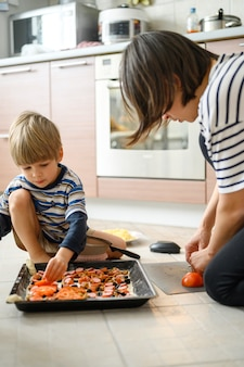 Mãe e filho juntos a cozinhar pizza