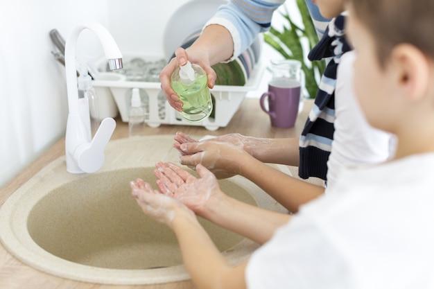 Mãe e filho lavando as mãos juntas