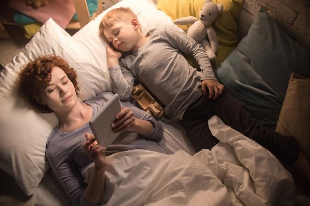 Mãe e filho lendo histórias na cama