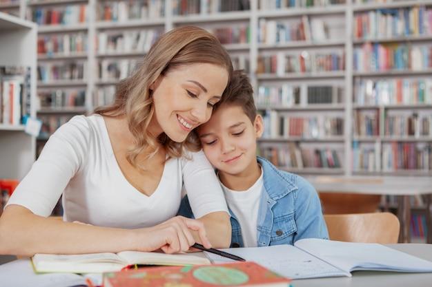 Mãe e filho lendo na biblioteca