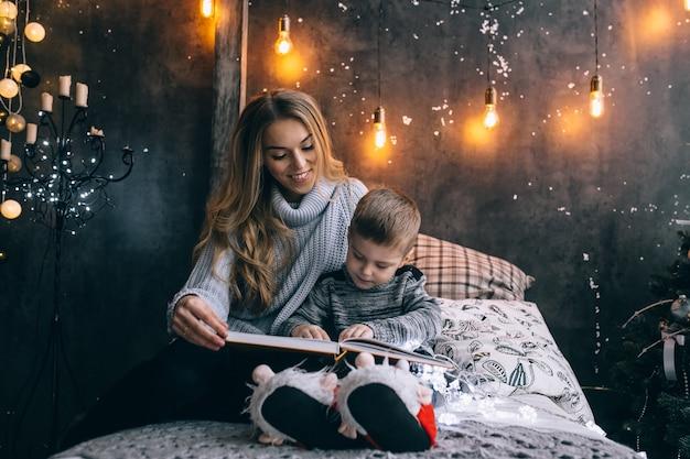 Mãe e filho lendo um livro na sala