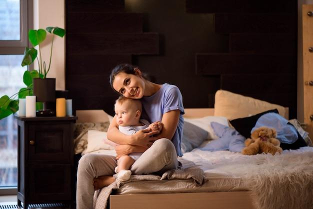 Mãe e filho menina criança brincando e abraçando na cama.