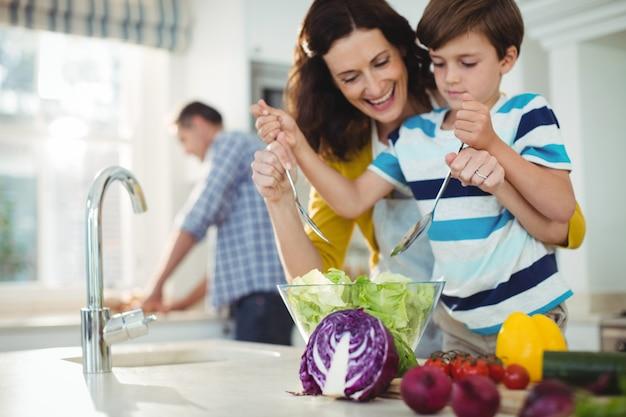 Mãe e filho misturando a salada na cozinha