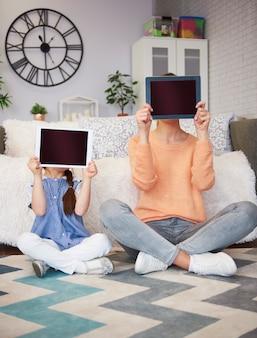Mãe e filho mostrando um tablet com espaço de cópia