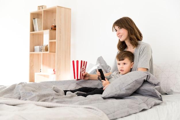 Mãe e filho na cama assistindo tv