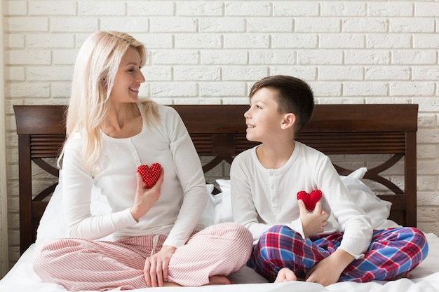 Mãe e filho na cama com pequenos corações