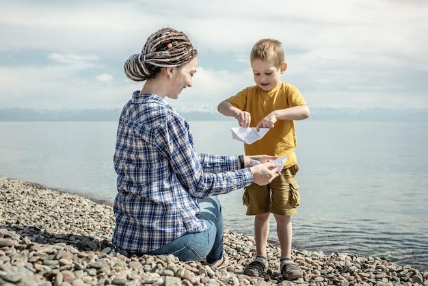 Mãe e filho na costa pedregosa de um grande lago estão brincando juntas e fazendo barquinhos de papel