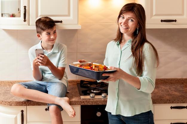 Mãe e filho na cozinha com comida