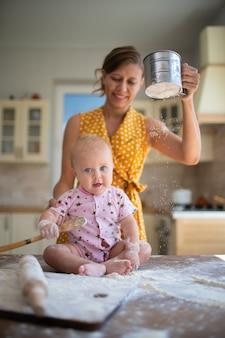 Mãe e filho na cozinha com farinha em casa