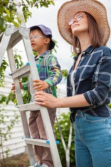 Mãe e filho na escada perto da árvore, jardinagem no jardim dos fundos
