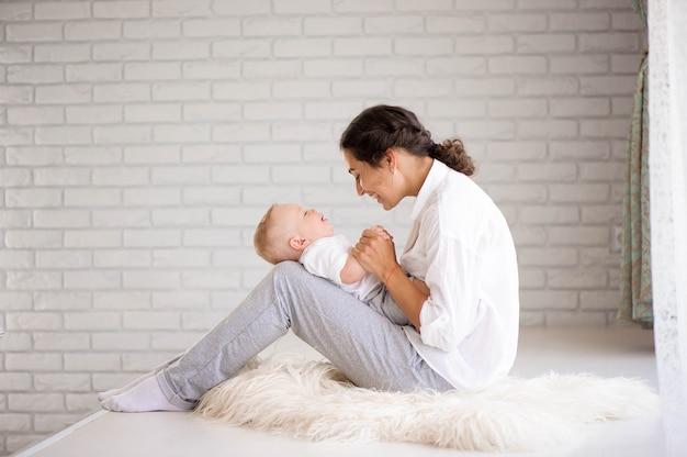 Mãe e filho na fralda brincando no quarto ensolarado. família se divertindo juntos.