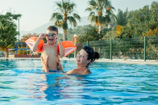 Mãe e filho na piscina ao ar livre criança aprendendo a nadar mulher e criança brincando na água férias de verão em família esporte ativo e saudável para crianças