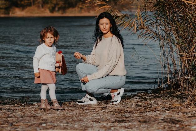 Mãe e filho na praia no fundo de um lago azul, mãe brinca com a filha no lago. natureza de outono