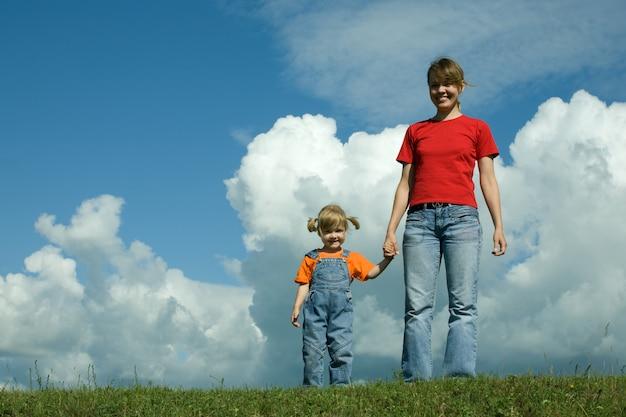Mãe e filho no campo sob o céu
