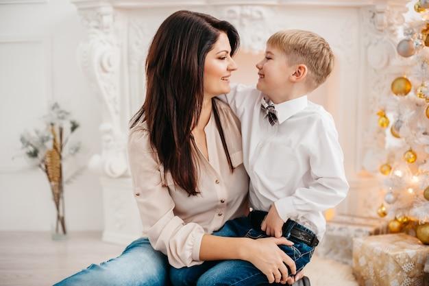 Mãe e filho no estúdio de natal. retrato de mãe feliz e filho sentado perto da árvore de natal.