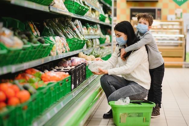Mãe e filho no supermercado juntos, eles vão às compras livremente sem máscara após a quarentena, escolhem comida juntos