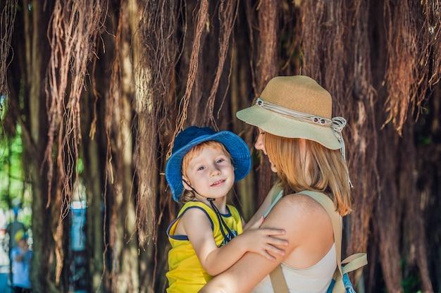 Mãe e filho nos viajantes do vietnã estão no fundo linda árvore com raízes aéreas