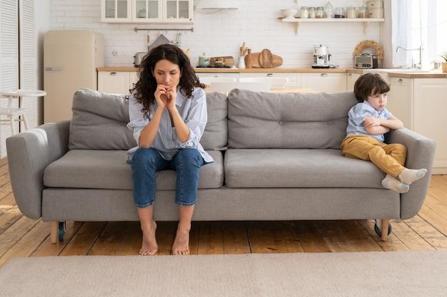 Mãe e filho ofendidos sentados no sofá da sala evitam conversar