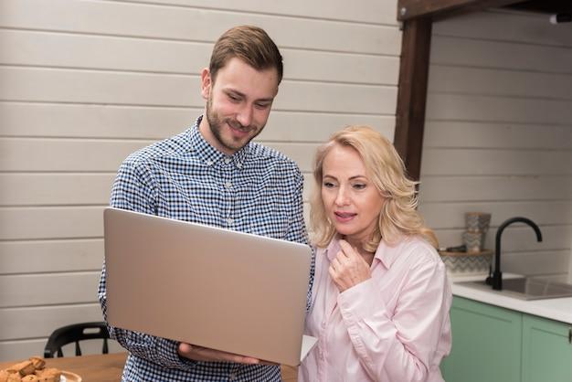 Mãe e filho olhando para laptop na cozinha