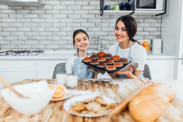 Mãe e filho pequeno na cozinha em casa aventais bonitos e felizes