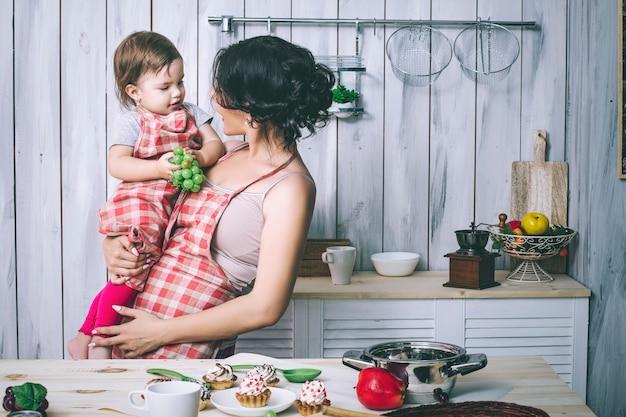 Mãe e filho pequeno na cozinha em casa com aventais