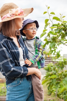Mãe e filho perto de árvore, jardinagem no jardim dos fundos