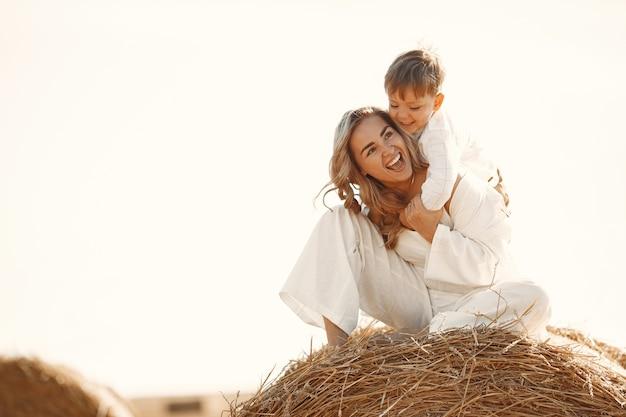 Mãe e filho. pilha de feno ou fardo no campo de trigo amarelo no verão. crianças se divertindo juntos.