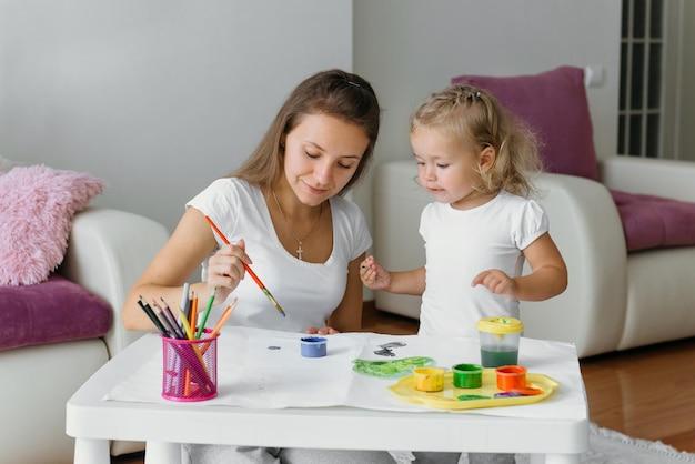 Mãe e filho pintando em casa, família criativa