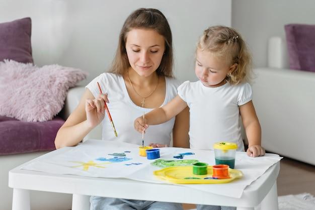 Mãe e filho pintando em casa