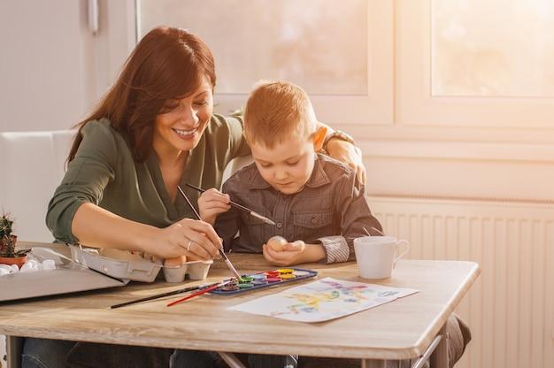 Mãe e filho pintando ovos de páscoa