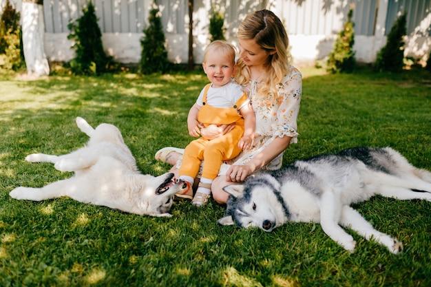Mãe e filho posando com dois cachorros na grama