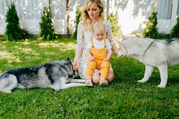 Mãe e filho posando com dois cachorros no jardim Foto Premium