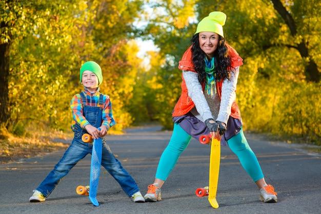 Mãe e filho posando com skate ao ar livre