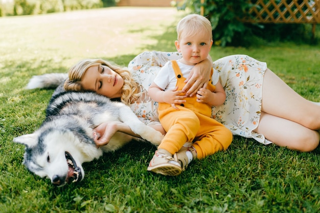 Mãe e filho posando com um cachorro na grama