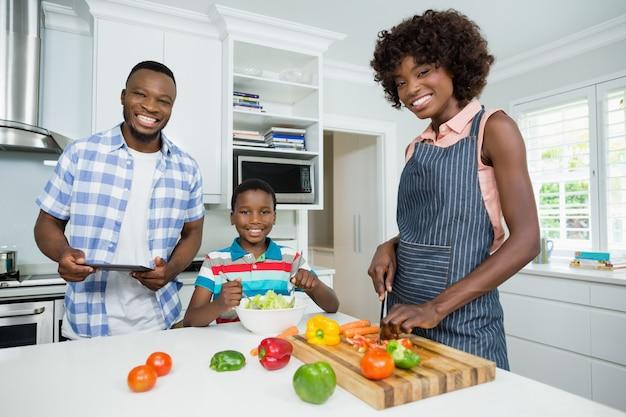 Mãe e filho preparando salada enquanto pai usando tablet digital na cozinha em casa