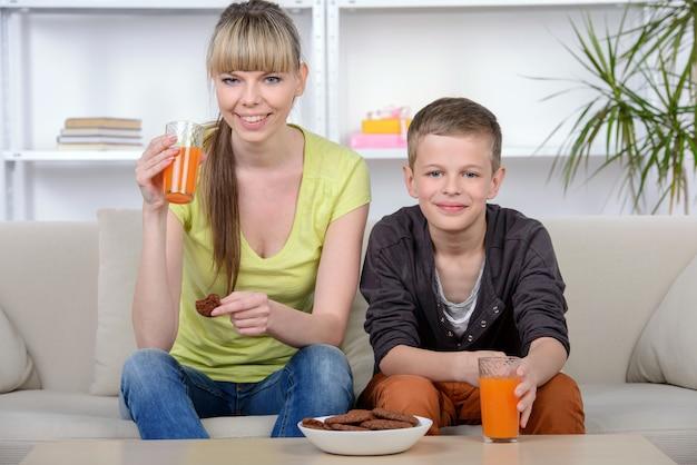 Mãe e filho que comem o café da manhã em casa.