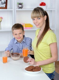 Mãe e filho que comem o café da manhã na cozinha.