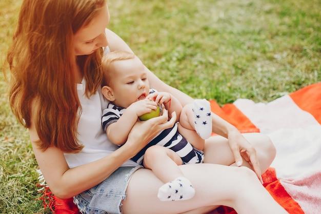 Mãe e filho relaxam no parque.