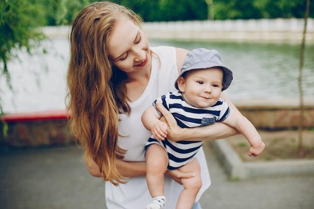 Mãe e filho relaxar no parque e caminhar ao redor do rio.