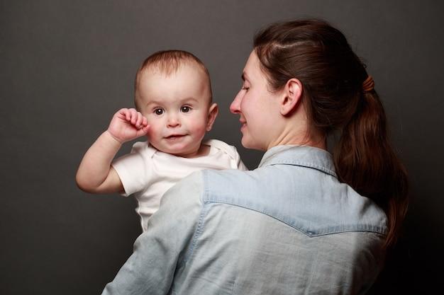 Mãe e filho se abraçando sobre um fundo cinza. maternidade