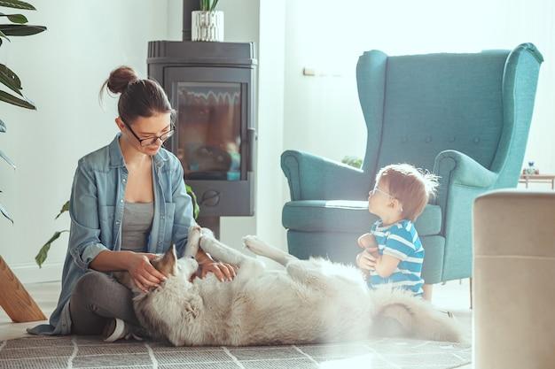 Mãe e filho se divertem e brincam com o cachorro em casa