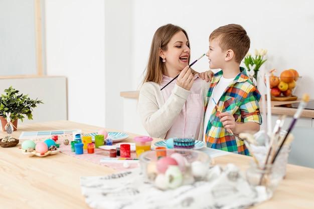 Mãe e filho se divertindo enquanto pinta ovos
