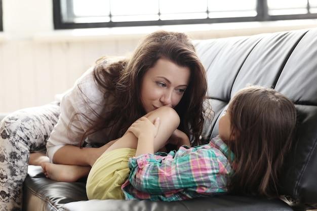 Mãe e filho se divertindo no sofá