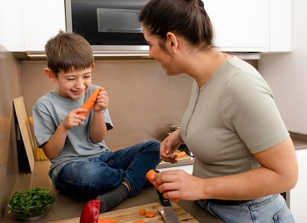 Mãe e filho segurando cenouras