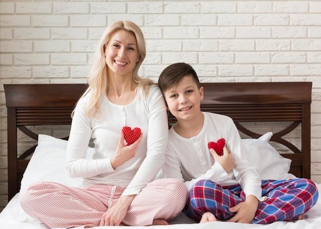 Mãe e filho segurando pequenos corações