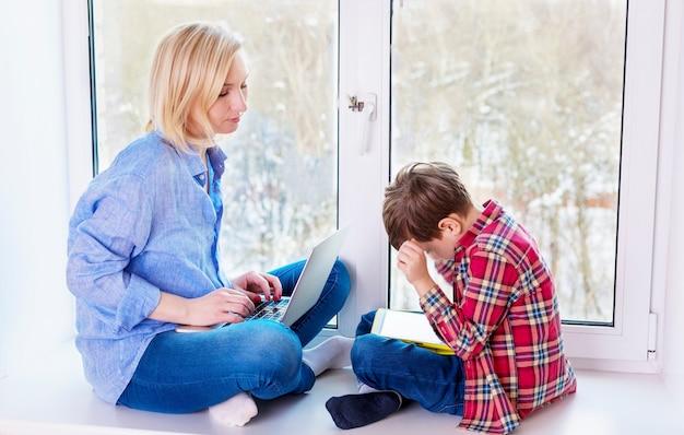 Mãe e filho sentado em um peitoril da janela com gadgets