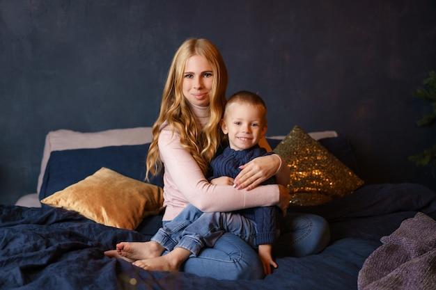 Mãe e filho sentado na cama em um abraço.