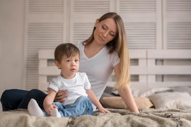 Mãe e filho sentado na cama